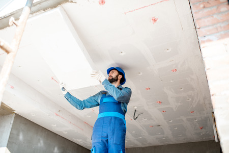 Builder warming building ceiling mounting foam panels on the construction site