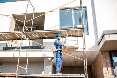Constructeur réchauffant une façade de bâtiment avec des panneaux de mousse se tenant sur les échafaudages sur le chantier de construction