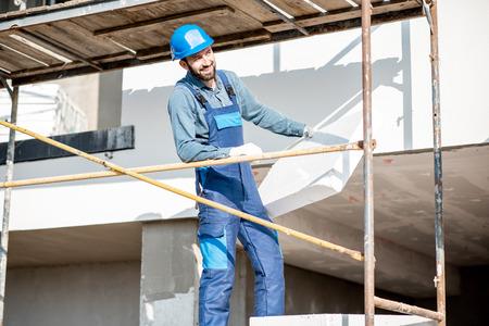 Divertente ritratto di un costruttore che riscalda la facciata di un edificio con pannelli di schiuma in piedi sulle impalcature del cantiere