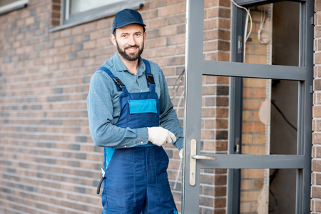 Builder in uniform installing a door lock into the entrance door of a new house outdoors Фото со стока