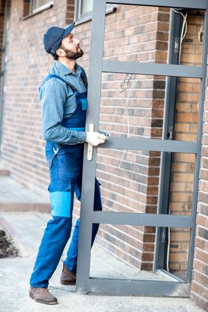 Builder in uniform installing aluminium entrance door of a new house outdoors