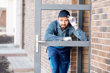 Funny portrait of a builder looking through the entrance door of a new house outdoors