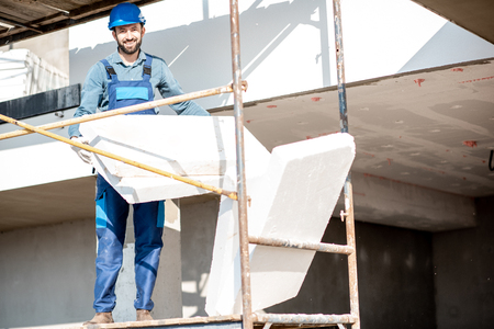 Portrait of a builder warming a building facade with foam panels standing on the scaffoldings on the construction site