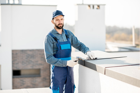 Builder in uniform mounting metal cover on the parapet of a new building Stock Photo