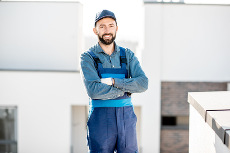 Portrait of a builder in uniform on the roof of a new white building outdoors