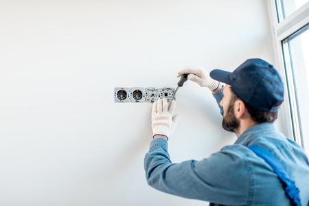 Elettricista in uniforme che monta prese elettriche sulla parete bianca all'interno Archivio Fotografico