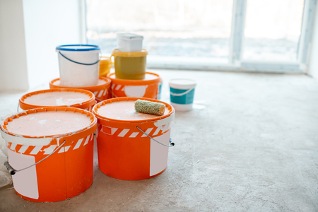 Buckets with building mix on the floor at the construction site indoors