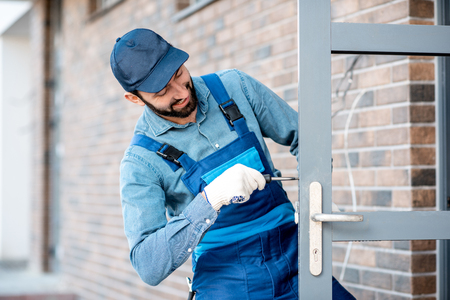 Builder in uniform installing a door lock into the entrance door of a new house outdoors 스톡 콘텐츠