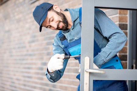 Builder in uniform installing a door lock into the entrance door of a new house outdoors Stock Photo