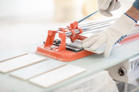 Gros plan sur un homme coupant des carreaux de céramique avec une machine pratique Banque d'images