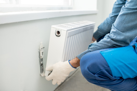 Workman mounting water heating radiator on the white wall indoors, close-up view Stockfoto