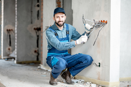 Portrait of an electrician mounting wiring for electric sockets on the construction site of a new building indoors