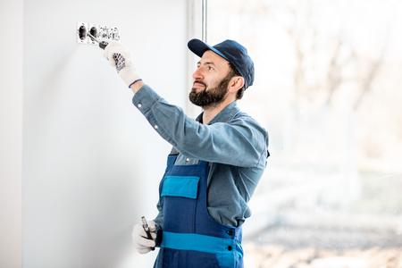 Elektricien in uniforme montage van stopcontacten op de witte muur binnenshuis