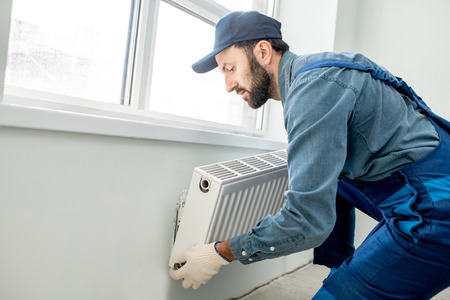 Workman mounting water heating radiator near the window in the white renovated living room
