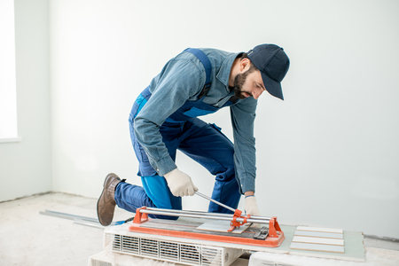 Arbeiter schneiden Keramikfliesen mit handlicher Maschine auf der Baustelle im Innenbereich