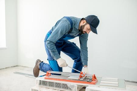 Ouvrier coupant des carreaux de céramique avec une machine pratique sur le chantier de construction à l'intérieur
