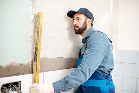 Workman in blue uniform checking the level while installing white ceramic tiles at the bathroom