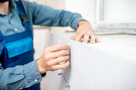 Workman in blue uniform inserting distance crosses installing ceramic tiles indoors, close-up view focused on the hands Stock fotó - 112134280