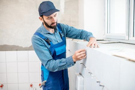 Ouvrier en uniforme bleu installant des carreaux de céramique blancs dans la salle de bain