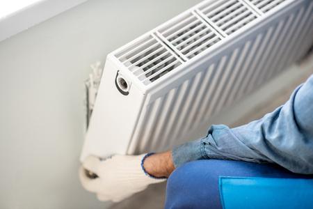 Operaio che monta il radiatore del riscaldamento dell'acqua sulla parete bianca all'interno, vista ravvicinata