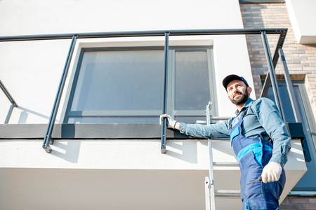 Builder in blue uniform mounting aluminium fence on the balcony of the new building Stock Photo