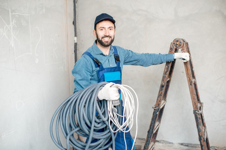 Portrait of a handsome electrician in uniform with electric cable indoors Imagens