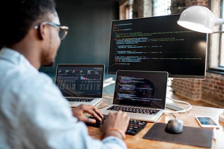 Programador masculino africano joven que escribe el código del programa que se sienta en el lugar de trabajo con tres monitores en la oficina. Imagen enfocada en la pantalla Foto de archivo