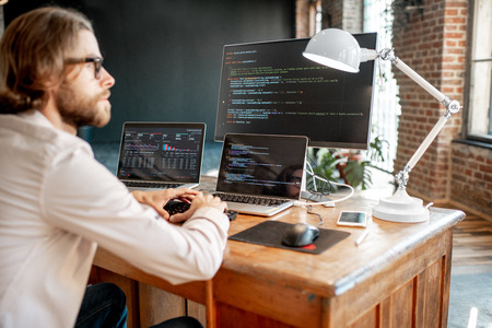 Young male programmer writing a program code sitting at the workplace with three monitors in the office. Image focused on the screen Standard-Bild