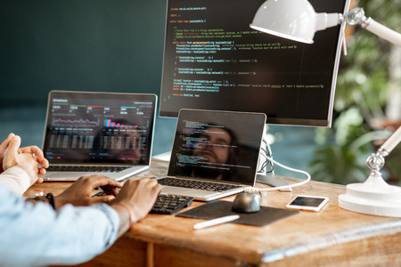 Programmers writing a program code sitting at the workplace with three monitors in the office. Cropped imaage with no face Stock Photo