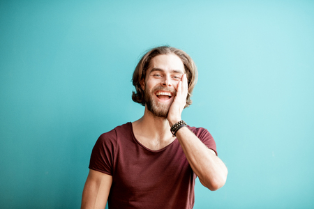 Emotional portrait of a young caucasian bearded man with long hair dressed in t-shirt on the colorful background