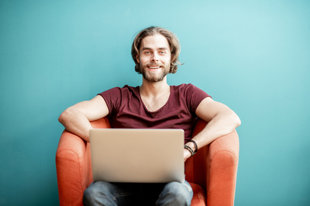 Portrait of a young caucasian bearded man with long hair dressed in t-shirt working with laptop on the chair on the colorful background