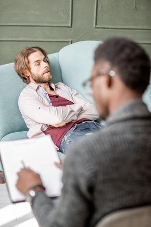 Jonge blanke man die een Afrikaanse psycholoog bezoekt die op de comfortabele bank ligt tijdens een psychologische sessie in het groene kantoor Stockfoto