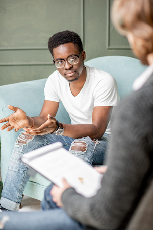 Young afro ethnicity man having a serious conversation with psychologist sitting on the comfortable couch during psychological session in the office Standard-Bild - 112136405