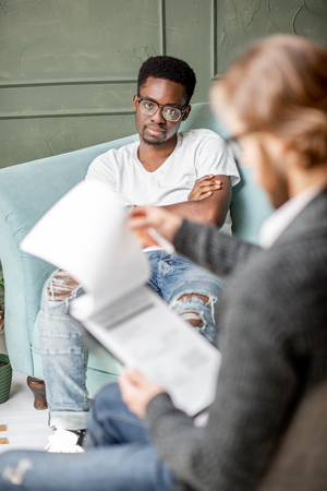 Young afro ethnicity man having a serious conversation with psychologist sitting on the comfortable couch during psychological session in the office