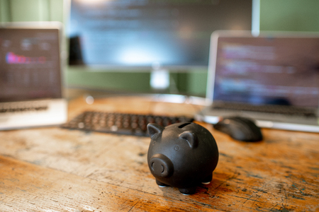 Black piggybank on the table with computers on the background Stock Photo - 112136837