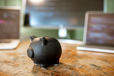 Black piggybank on the table with computers on the background