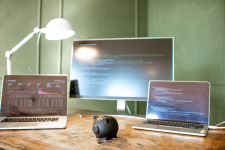 Black piggybank on the table with computers on the background Stock Photo - 112372417