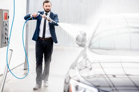 Geschäftsmann im Anzug, der sein Luxusauto mit Waschpistole auf einer Selbstbedienungs-Autowäsche im Freien wäscht?