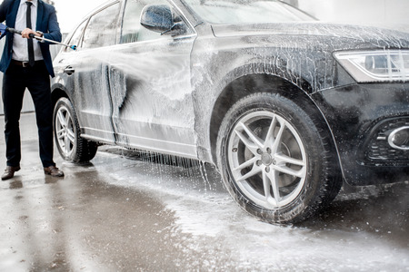 Close-up of a car under the water jet during the washing process on a self service car wash 스톡 콘텐츠