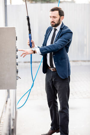Businessman washing car on a self service car wash, standing with washing gun near the automate