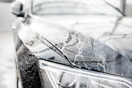 Close-up of a luxury black car during the washing process with water dropes outdoors