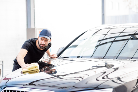 Professional washer in t-shirt and cap wiping a car hood with yellow microfiber at the open air car wash
