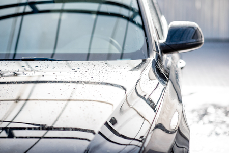Close-up of a clean car with water dropes after the washing