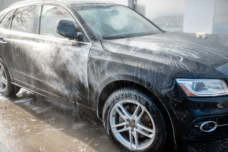 Close-up of a car under the water jet during the washing process on a self service car wash Banque d'images