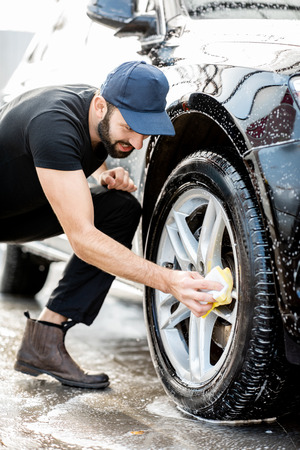 Professional washer in black uniform and cap wiping with sponge car wheel during the washing process outdoors 版權商用圖片