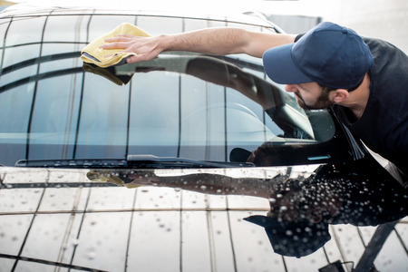 Professional washer in t-shirt and cap wiping windshield with yellow microfiber at the open air car wash