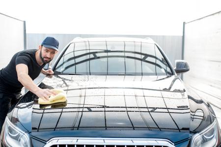 Professioneller Wascher in T-Shirt und Mütze, der eine Motorhaube mit gelber Mikrofaser an der Open-Air-Autowaschanlage abwischt