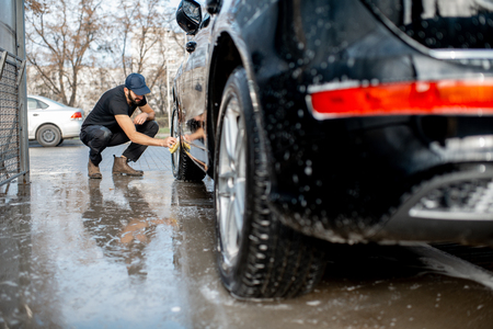 Professional washer in black uniform and cap wiping with sponge car wheel during the washing process outdoors Stok Fotoğraf