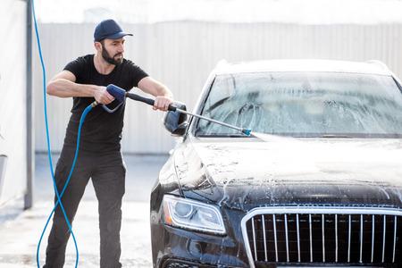 Rondella professionale in uniforme nera che lava auto di lusso con pistola ad acqua su un autolavaggio all'aperto Archivio Fotografico