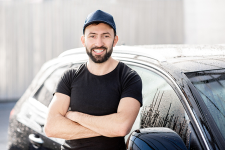 Portrait of a professional washer in black t-shirt and hat standing near the car outdoors Stock Photo - 112373101